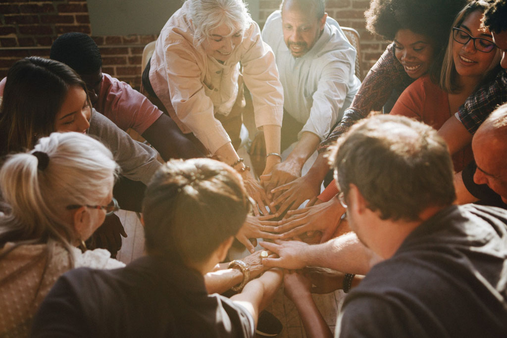 Group of volunteers with hands connected in middle of circle