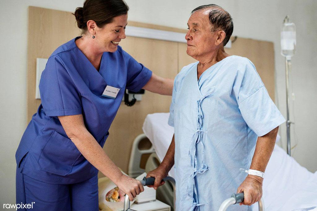 Nurse helping elderly man walk with frame